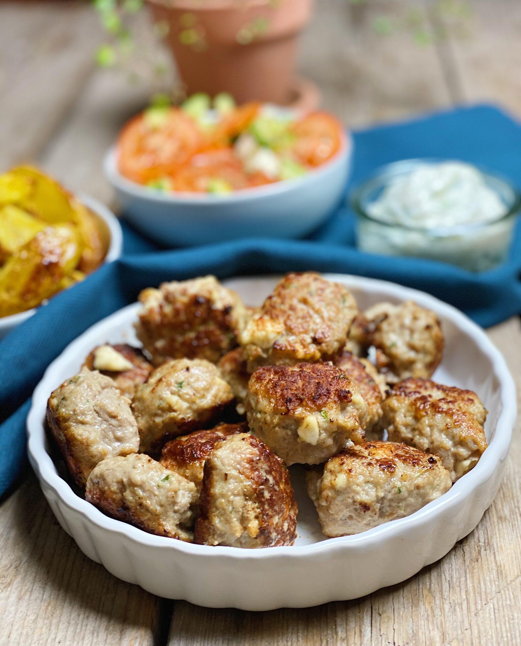 Græske frikadeller serveret med kartfoffelbåde, tomatsalat og tzatziki