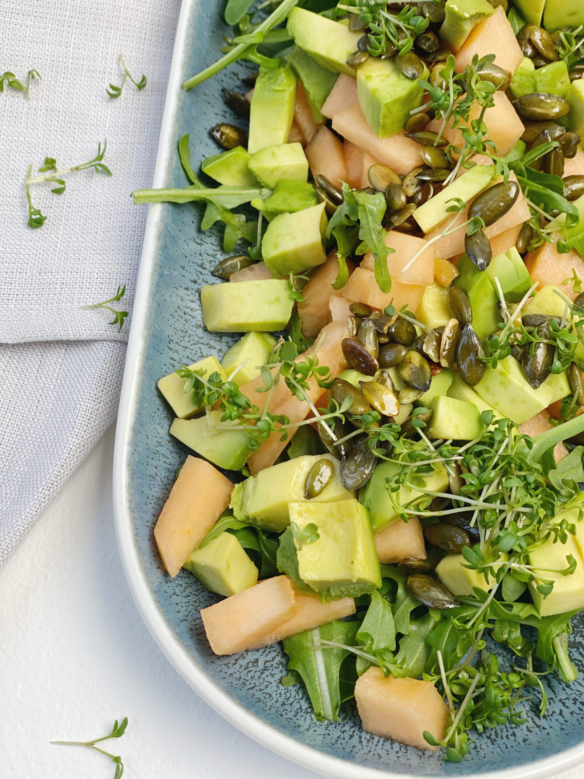 Rucolasalat med avocado, galiamelon, karse og græskarkerner close up