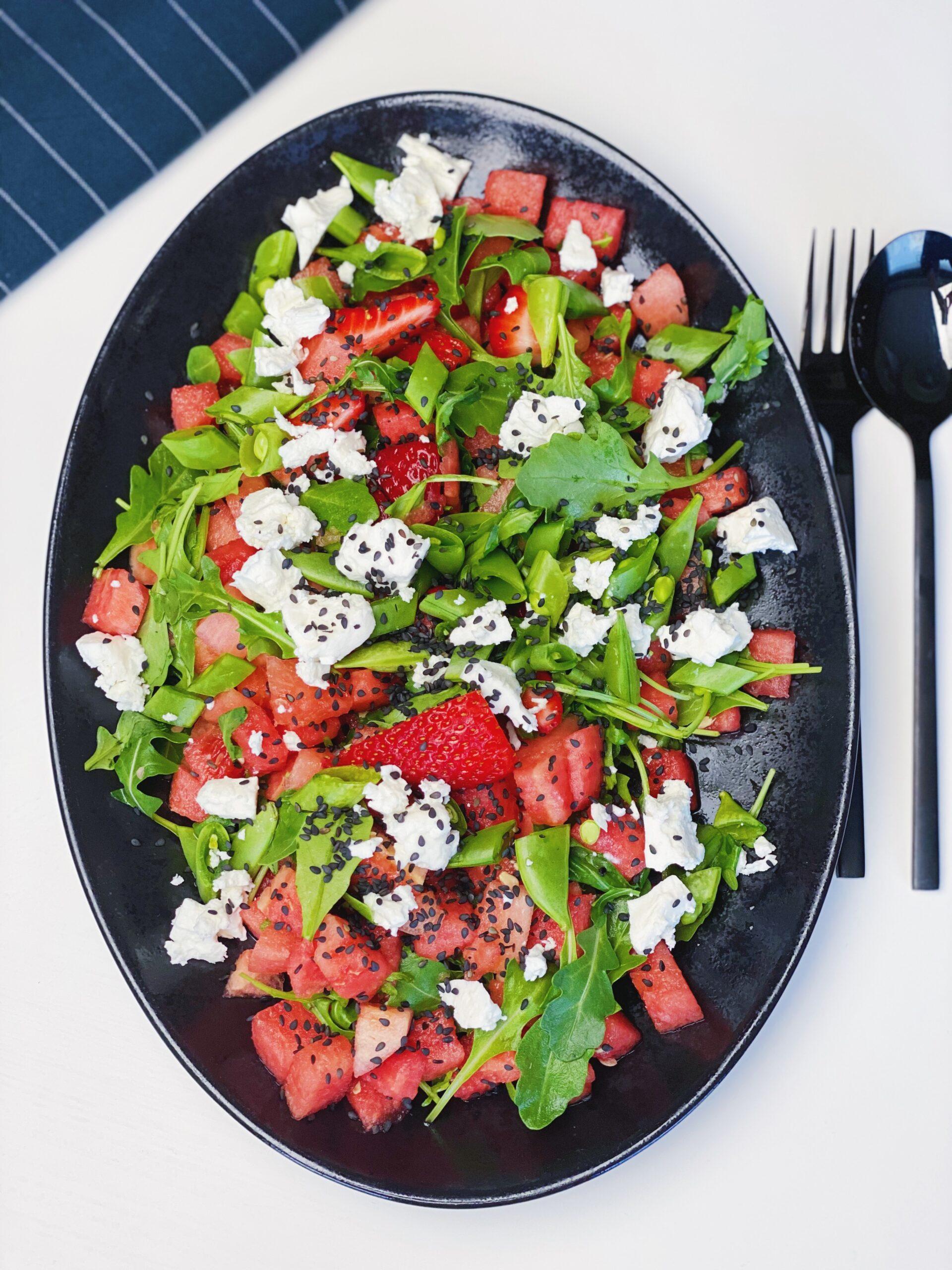Sommersalat med vandmelon og jordbær på et sort fad