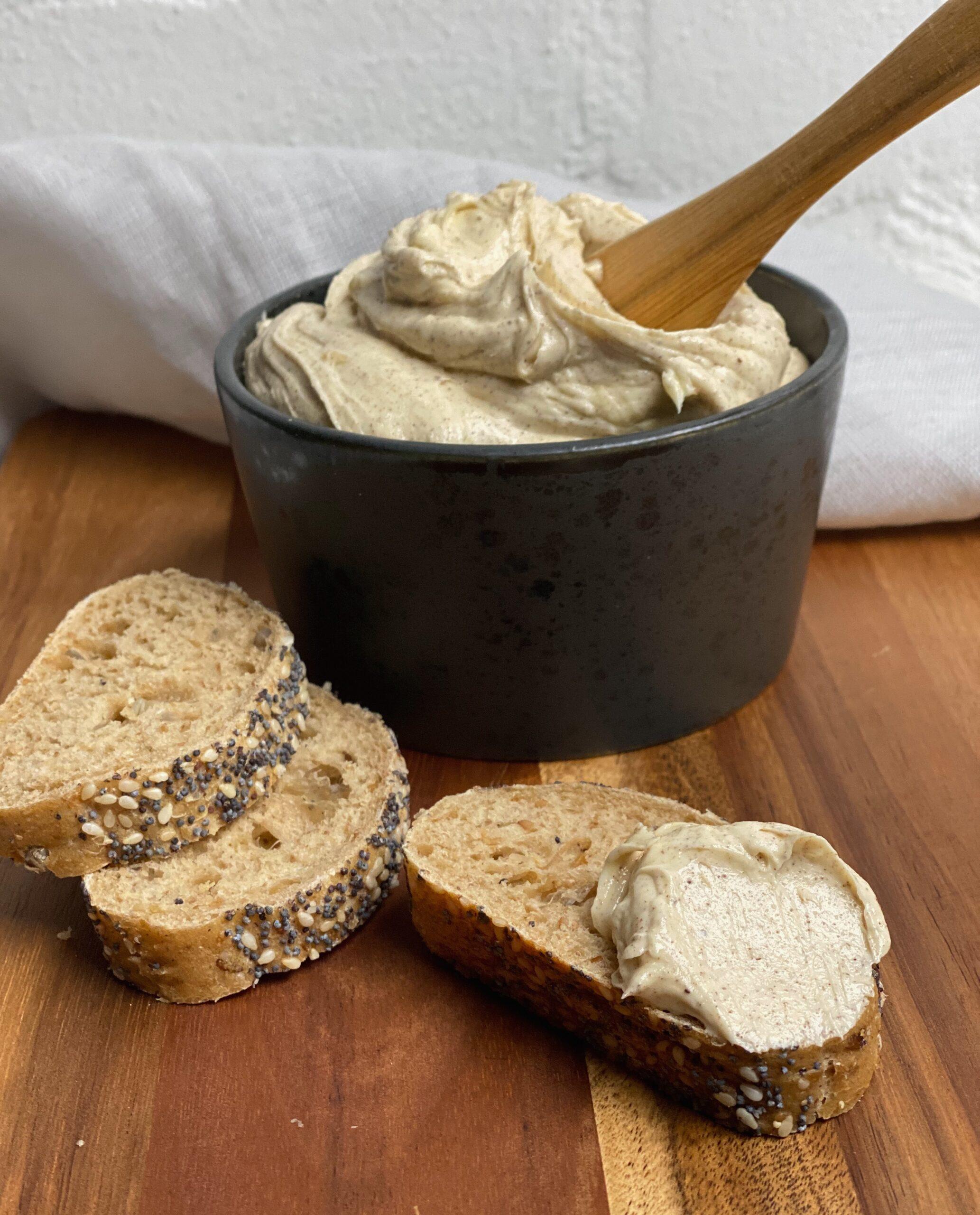 Pisket brunet smør i en skål med nogle skiver brød foran med smørret på