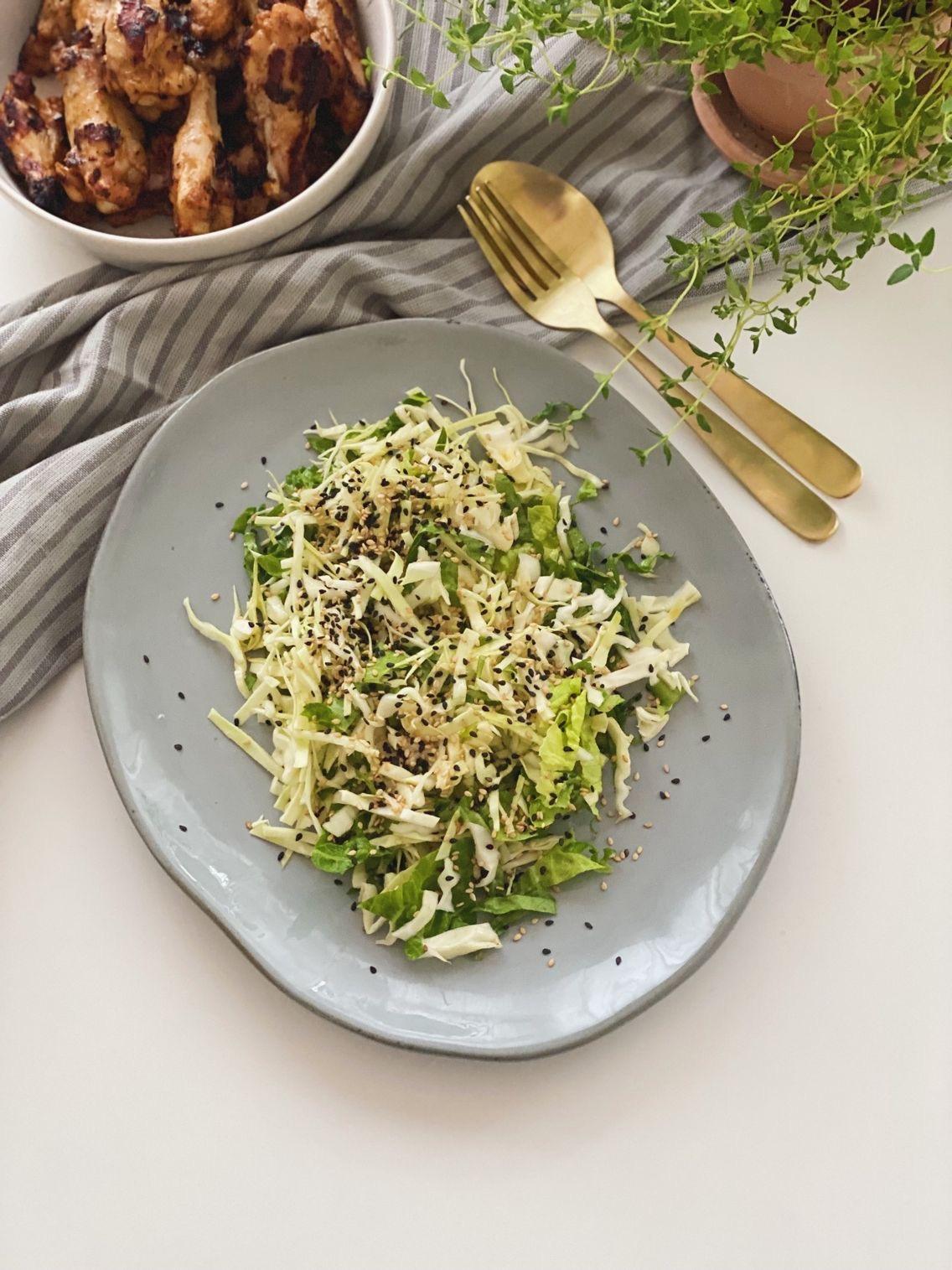 Spidskålsalat med ingefærdressing på et gråt fad set oppefra med kyllingevinger i baggrunden og frisk timian i en lerpotte