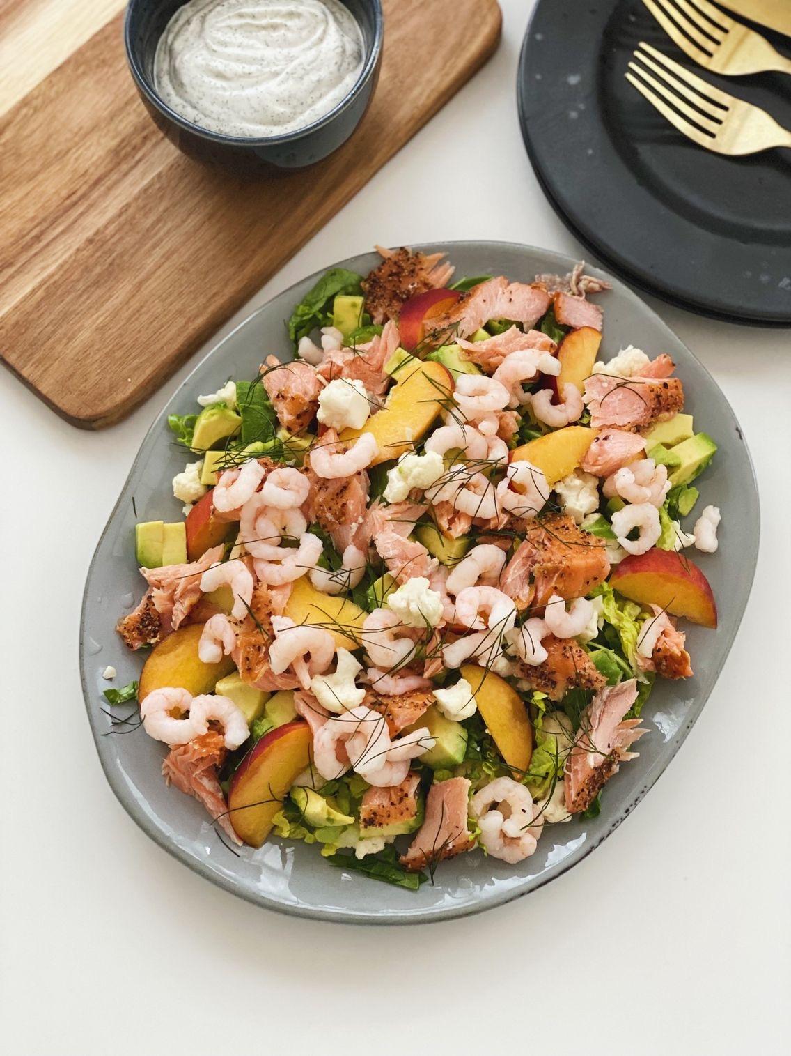 Måltidssalat med laks, rejer og ferskner på et gråt fad set oppefra med en skål med cremefraichedressing ved siden af som er i en sort skål. Der står til højre tallerkner hvor der ligger bestik på.
