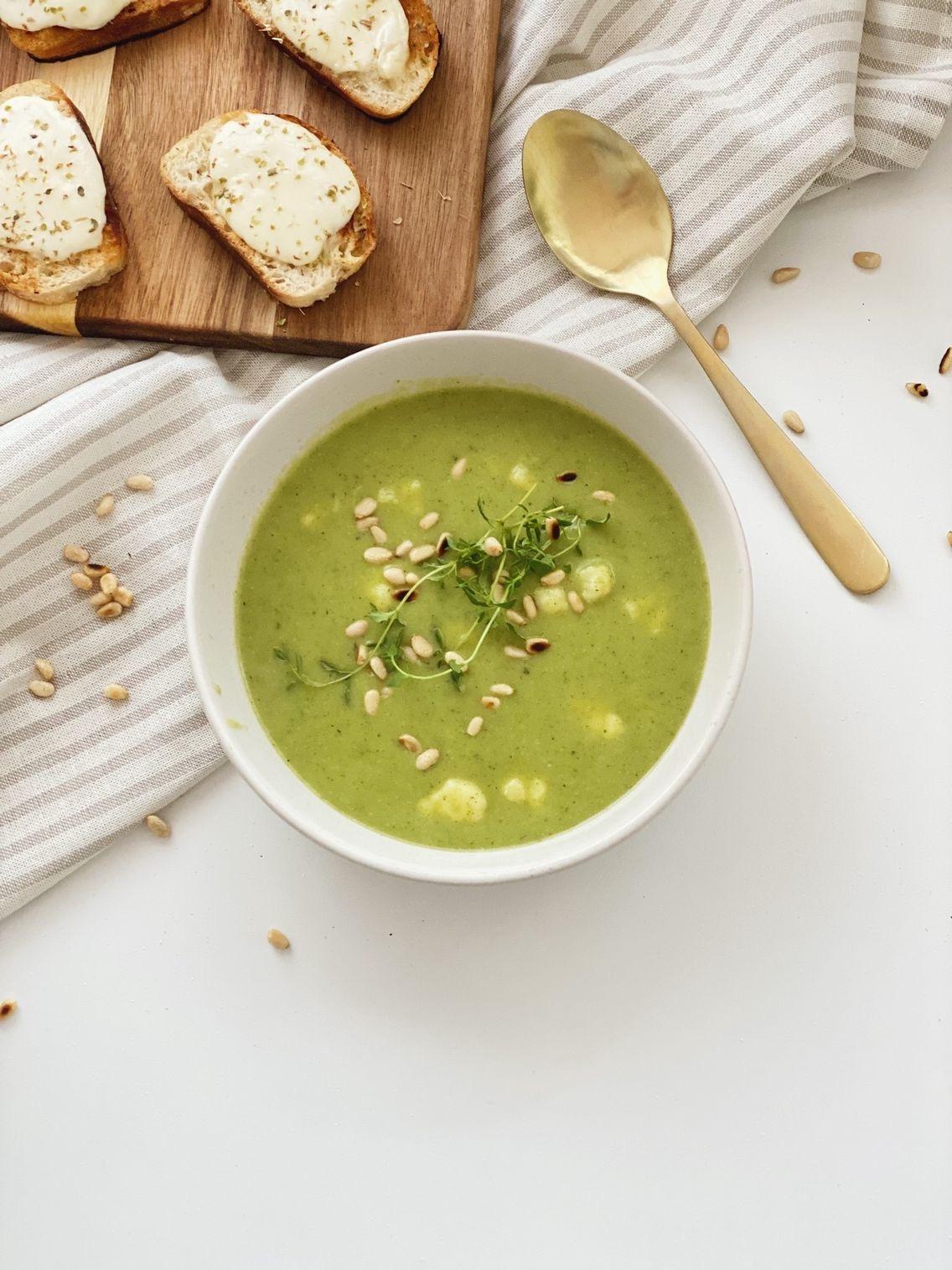 Broccolisuppe i en skål pyntet med ristede pinjekerner. Der ligger pinjekerner rundt på bordet, en ske ved siden af og ostebrød på et spækbræt ved siden af.