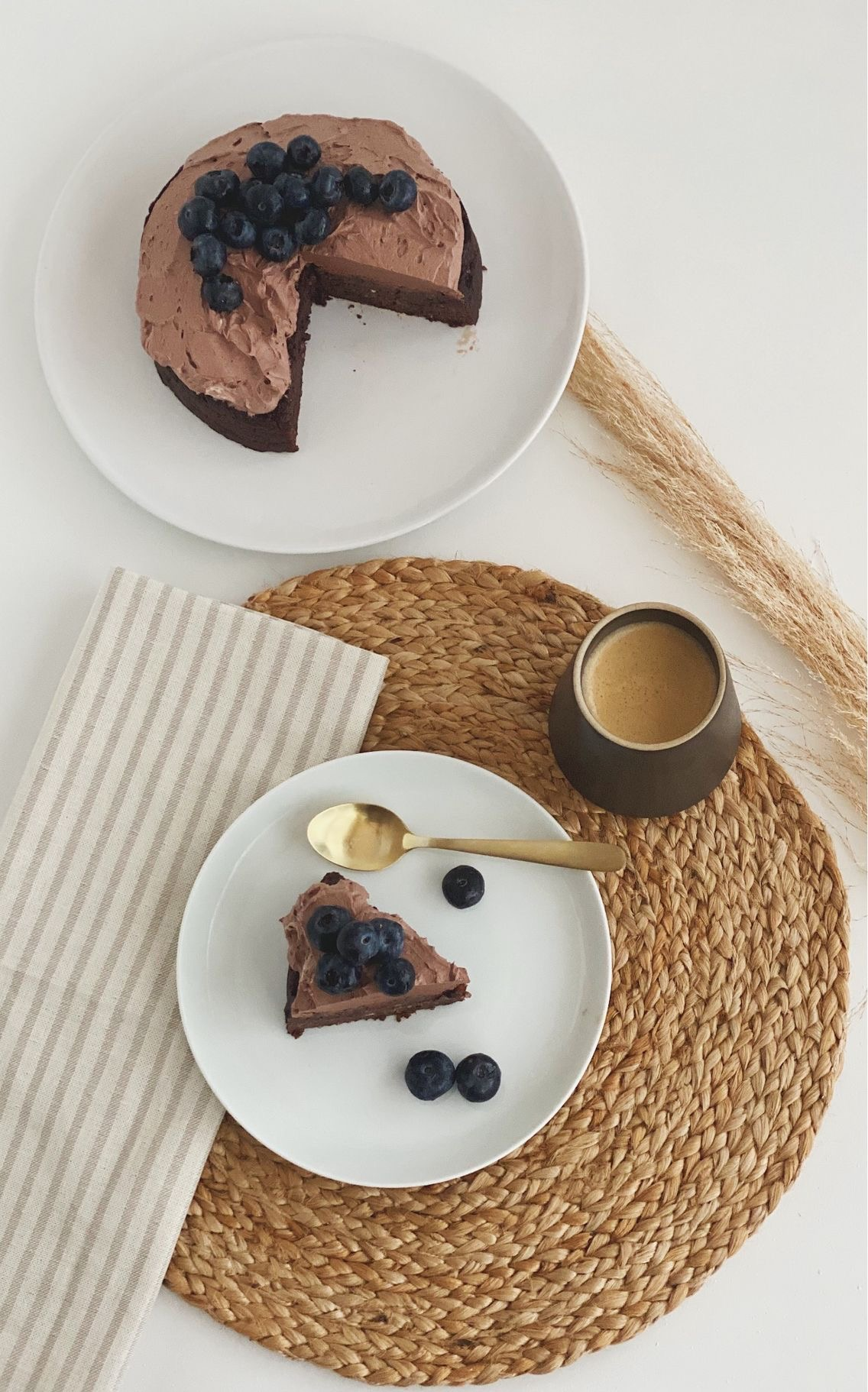 Chokoladekage med avocado med kakaosmørcreme og pyntet med blåbær på toppen, set oppefra og den hele kage ses + et enkelt stykke for sig selv og en kop kaffe som står på en siv dækkeserviet
