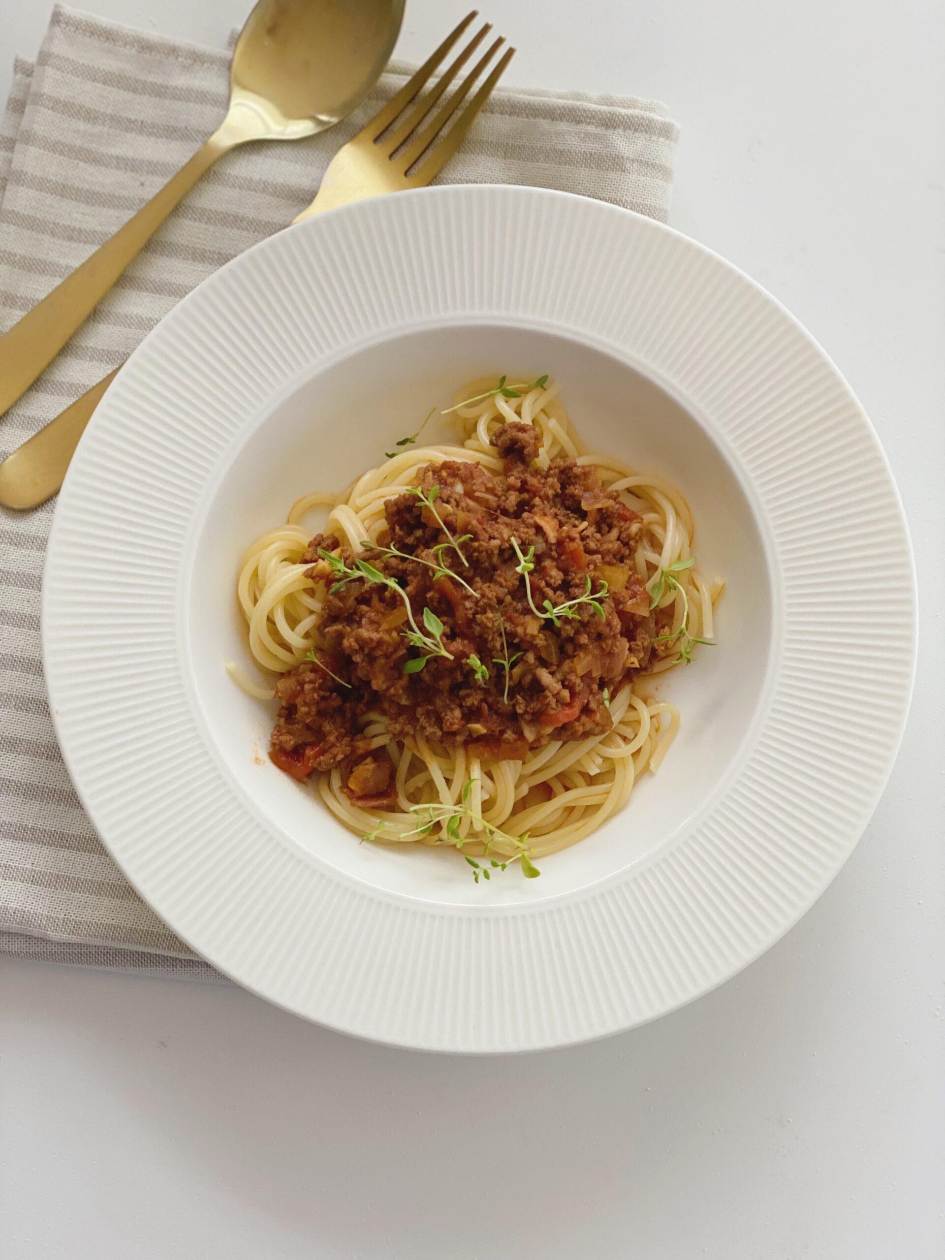 Spaghetti bolognese set oppe fra, hvor hele tallerkenen er synlig og der ligger en ske og en gaffel ved siden af oven på en stribet serviet