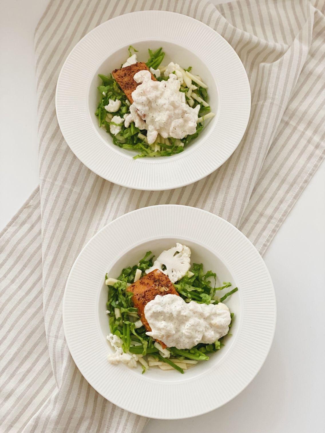 Varmrøget laks med rejesalat i to dybe tallerkner set oppe fra. de dybe tallerkner er placeret ovenpå en stribet serviet.
