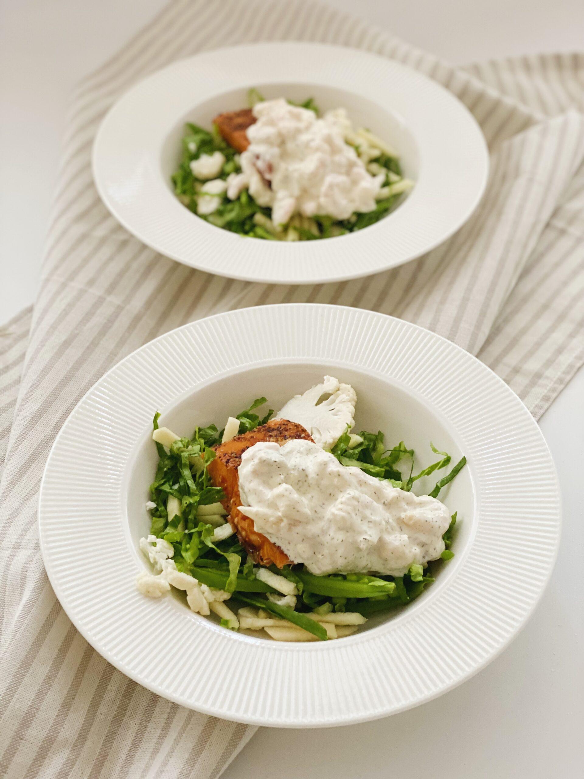 Varmrøget laks med rejesalat i to dybe tallerkner set skråt ind fra og tæt på den forreste tallerken. De dybe tallerkner er placeret ovenpå en stribet serviet.